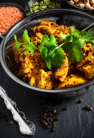 curry: Bombay spiced potatoes and cubed chicken thighs with coriander leaves  Shot in natural light with lentils and chickpeas  The perfect image for a restaurant cover design  Stock Photo