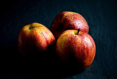 Attractively lit Royal Gala apples with water droplets against a dark background  Copy space  photo