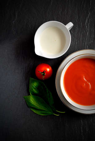 Overhead shot of fresh tomato soup with single cream, tomato and basil herbs. Selective lighting. Copy space. photo