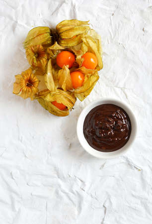 Overhead shot of ripe Physalis fruits with a bowl of melted dark chocolate dip. Copy space. photo