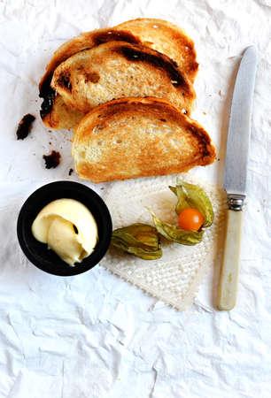 melba: Tiro de arriba de un desayuno continental, francés tostadas Melba casero con mantequilla y physalis fruta. Copie el espacio.