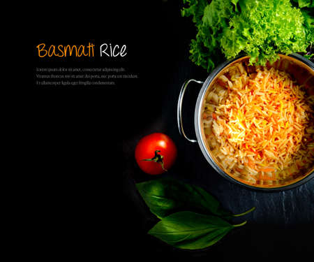 Aerial view of fresh Indian Basmati coloured rice with fresh salad and tomatoes against a dark background. Extended copy space. Banque d'images