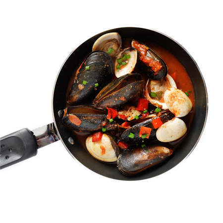 seafood soup: aerial view of cooked freshwater mussels and clams in a spicy red pepper sauce with chives. Copy space.