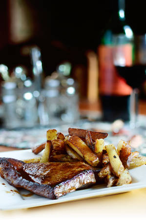 pub food: Grilled sirloin steak with fries, plated and ready to serve. The perfect image for your menu. Copy space. Stock Photo