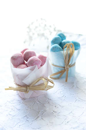favours: Pink and blue candy bonbons in tissue packets on a lace table. Concept image for childrens party or wedding favours. Copy space.