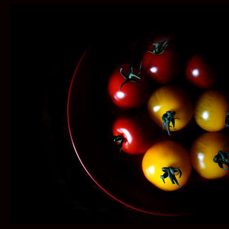 selectively: Aerial image of selectively lit amber & rosso vine tomatoes against black. Copy space. Stock Photo