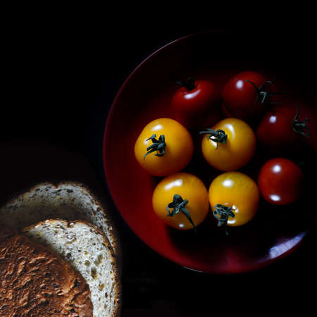 selectively: Aerial image of selectively lit amber & rosso vine tomatoes with sliced granary bread against black. Copy space.