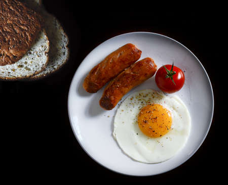 selectively: Aerial image of selectively lit rosso vine tomato with sliced granary bread, sausage and fried egg. Copy space.
