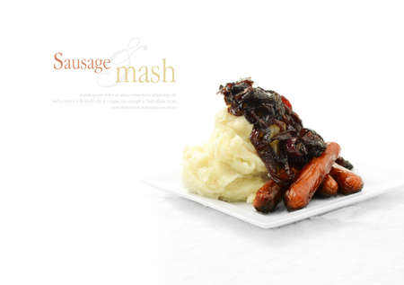 fayre: Traditional English fayre, grilled pork sausages with creamy mashed potatoes drizzled with caramelized red onions poached in red wine. Extended copy space.