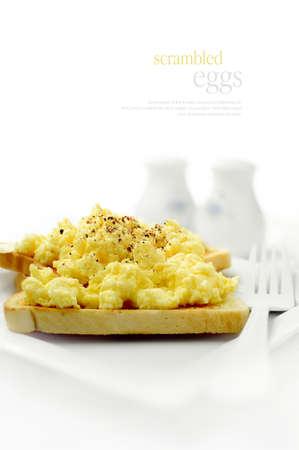 huevos revueltos: Huevos frescos suaves y esponjosas revueltos sobre una tostada de grano entero de trigo sobre un fondo blanco. Copiar el espacio. Foto de archivo