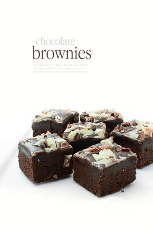 brownie: Freshly baked chocolate brownies with brown and white chocolate curls against a white background. Copy space.