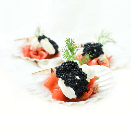 Tomato, cream cheese and caviar canapes with garnish against a white background. Copy space. photo