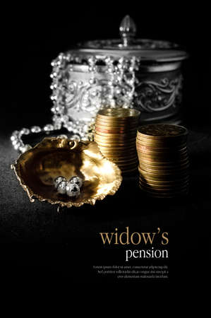 jewellery box: Concept image for widows pension. Creatively lit scene of antique silver jewellery box, a string of pearls with stacked coins against a dark background. Copy space. Stock Photo