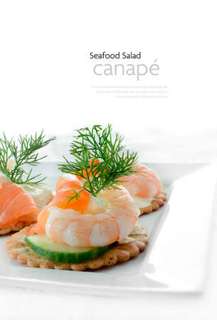 starter: Delicious soft cream cheese and Tiger Prawn and smoked Salmon canapes with dill garnish against a white background. Copy space.