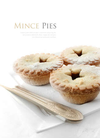 Sugar frosted festive mince pies against a white background. Copy space.