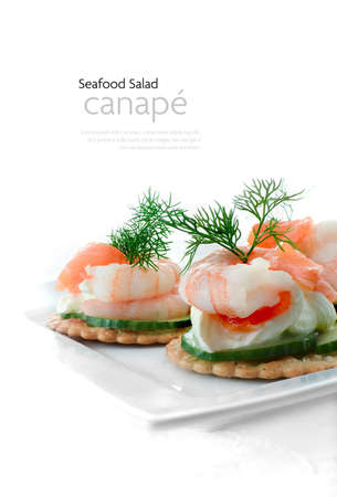 Delicious soft cream cheese and Tiger Prawn and smoked Salmon canapes with dill garnish against a white background. Copy space.