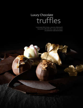 Luxury truffle chocolates on a bed of dark chocolate splinters and shards. Concept image for a little luxury. Copy space.