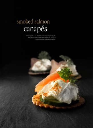 Creatively lit smoked salmon canapes against a black background. Copy space.