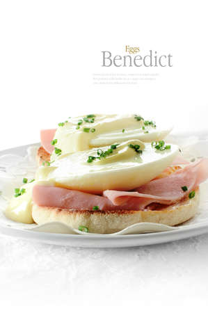 uk cuisine: Fresh, delicious eggs benedict on warm muffins with Parma ham against a white background. Copy space. Stock Photo