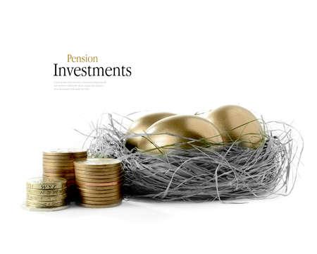 Gouden gans eieren geplaatst in een authentiek ogende gras nest tegen een witte achtergrond met het beeld gekleurd brons en grijstinten. Concept afbeelding voor pensioen sparen en beleggen. Exemplaar ruimte.