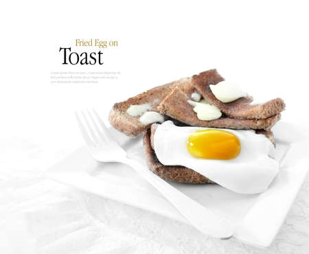 sunny side up: Delicious fried egg on wholemeal buttered toasted bread against a white background. Copy space. Stock Photo