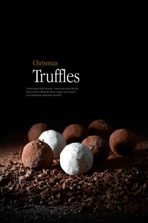 creatively: Creatively lit Christmas truffles on a bed of dark chocolate shards against a dark background. Copy space.