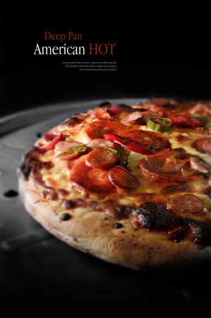 Selective focus on a sizzling deep pan American hot pizza against a dark background. Copy space.