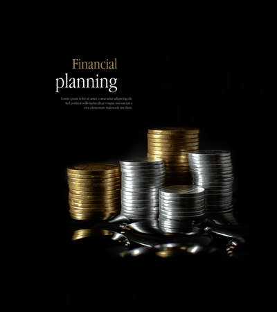 Concept image for financial planning. Creatively lit, stacked generic gold and silver coins representing client investment or savings. Copy space.