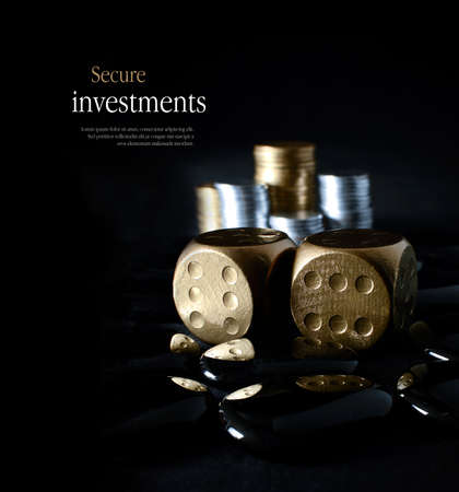 Concept image for secure financial planning. Creatively lit, stacked generic gold and silver coins representing client investment or savings with dice representing risk. Copy space.