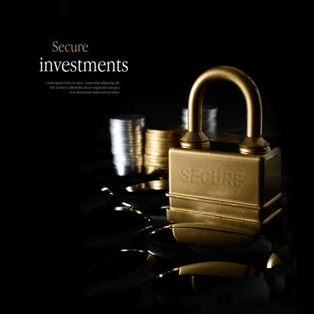 financial security: Concept image for secure financial planning. Creatively lit, stacked generic gold and silver coins representing client investment or savings with a gold padlock representing security. Copy space. Stock Photo