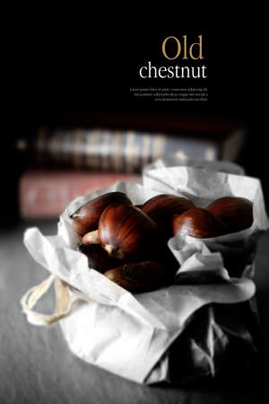 endearment: Concept image for the expression old chestnut, an English expression for endearment. Chestnuts against antique books and a dark background. Copy space.