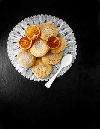 Aerial view of home meade shortbreads with caramalised orange segments against black slate. Copy space.