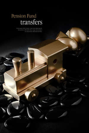 creatively: Creatively lit concept image for pension transfers. Gold wooden train with gold eggs against black. Copy space.