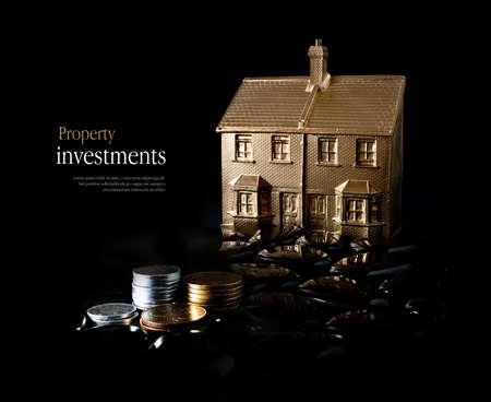 不動産投資のためのコンセプト イメージ創造的な金鉱の家および黒い背景に対して積み上げ硬貨を点灯します。スペースをコピーします。