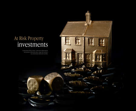 Concept image for at risk property investment. Creatively lit gold house and dice against a black background. Copy space.