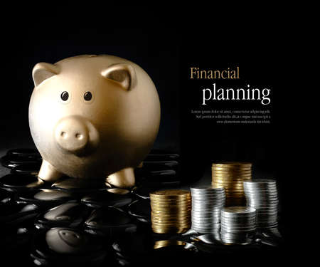Concept image for financial planning. Creatively lit gold piggy bank and stacked coins against a black background. Copy space.