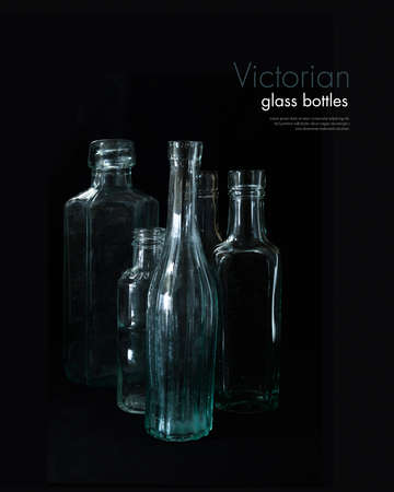 creatively: Creatively lit antique genuine Victorian glass bottles against a dark background. Copy space. Stock Photo