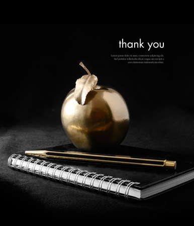 wealth concept: A concept image for rewards and success. A gold apple on a notebook with a gold pen against a black background. Copy space.