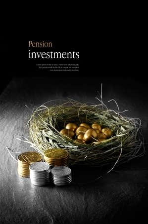 創造的な年金の投資のための概念イメージを点灯します。黒い背景に対して積み上げコインで草の鳥の巣の金の卵。スペースをコピーします。