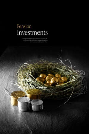 Creatively lit concept image for pension investments. Gold eggs in a grass birds nest with stacked coins against a black background. Copy space.