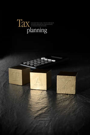 tax: Concept image for tax management and tax return. Creatively lit calculator and gold blocks against a black background. Copy space.