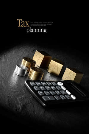 Concept image for tax management and tax return. Creatively lit calculator and gold blocks and coins against a black background. Copy space.