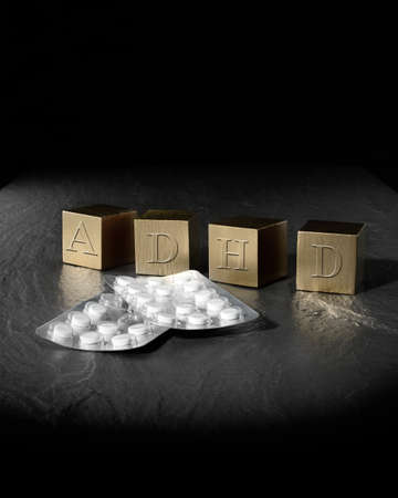 Creative concept image for Attention Deficit Hyperactivity Syndrome or ADHD. Gold wooden blocks and medication tablets against a black background. Copy space. photo