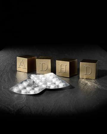 Image creatief concept voor Attention Deficit Hyperactivity Syndroom of ADHD. Goud houten blokken en medicatie tabletten tegen een zwarte achtergrond. Exemplaar ruimte.