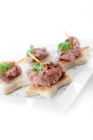 pate: Chicken liver pate canapes with orange peel and parsley garnish against a white background. Copy space. Stock Photo