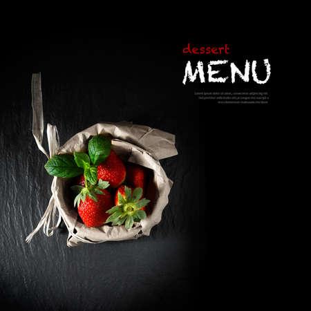 fresa: Imagen del concepto creativa iluminado por una pizarra men� de postres. Fresas frescas y hojas de menta en una bolsa de papel marr�n. Copiar el espacio.