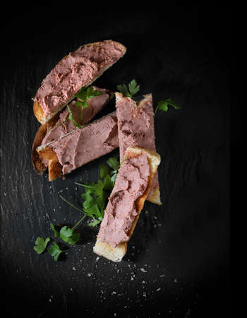 creatively: Creatively lit aerial shot of chicken liver pate on toast with parsley garnish. Copy space. Stock Photo