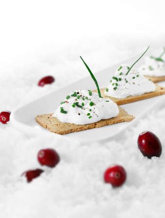 Selective focus of cream cheese canapes with chives against a white background on crushed ice. Copy space. photo