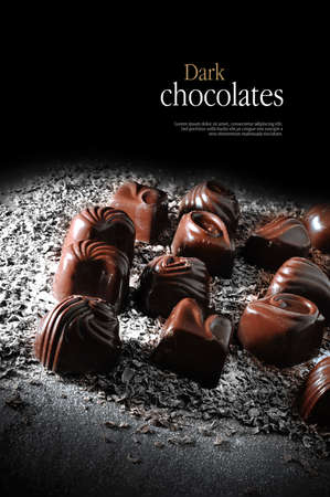 Creatively lit dark chocolate liqueurs against a dark background. Copy space.