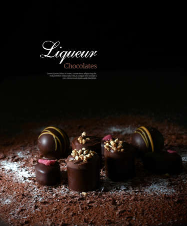 dessert: Creatively lit dark liqueur chocolates against a dark background. Copy space. Stock Photo